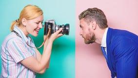 Il est photog?ne Jolie femme ? l'aide de la cam?ra professionnelle Homme d'affaires posant devant le photographe f?minin images stock