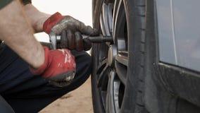 Il fabbricante automobilistico svita i bulloni della ruota per cambiare la ruota dell'automobile video d archivio