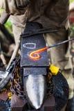 Il fabbro curva il fermaglio del ferro con il martello sull'incudine Immagine Stock