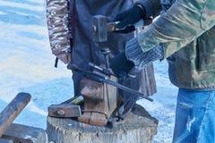 Il fabbro forgia i chiodi per i ferri di cavallo Fotografia Stock