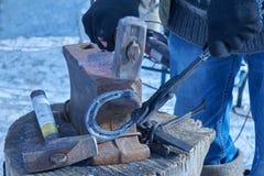 Il fabbro forgia il ferro di cavallo sull'incudine Fotografie Stock Libere da Diritti