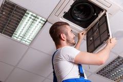 Il fabbro installa il sensore sulla copertura di ventilazione immagine stock libera da diritti
