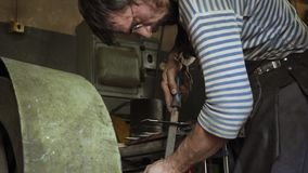 Il fabbro sta lavorando con il dettaglio del ferro e sta usando un archivio stock footage