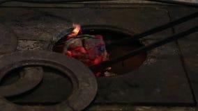 Il fabbro utilizza una vecchia pala per rifornire sulle fiamme dentro la forgia del carbone ai fini di metallo di lavoro stock footage