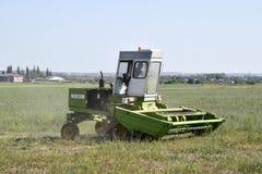 Il falciatore nel campo falcia l'erba per fieno Fotografie Stock Libere da Diritti