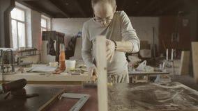 Il falegname professionista collega due bordi lucidati di legno mobilia complessivo video d archivio