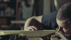 Il falegname tagliuzza il pezzo in lavorazione di legno con il movimento lento dell'presa-aereo archivi video