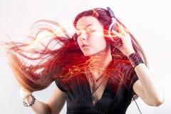 Il fan della ragazza canta e balla ascoltare la musica La giovane donna castana in grandi cuffie gode della musica fotografia stock libera da diritti