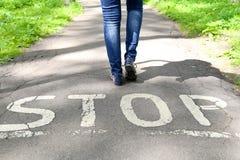 Il fanale di arresto dipinto sulla strada e sulle gambe femminili Fotografia Stock Libera da Diritti