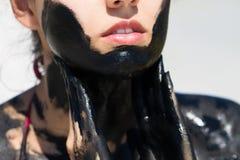 Il fango curativo sulla pelle di bella ragazza Immagine Stock