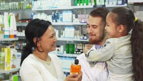 Il farmacista con una ragazza in lei armi e sua madre sceglie un rimedio in una farmacia immagini stock