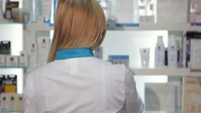 Il farmacista femminile gira intorno alla farmacia video d archivio