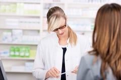 Il farmacista femminile legge una prescrizione della medicina immagini stock libere da diritti