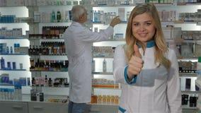 Il farmacista femminile mostra il suo pollice su alla farmacia video d archivio