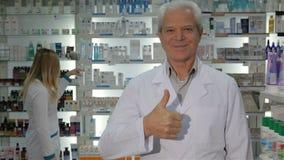Il farmacista maschio mostra il suo pollice su video d archivio