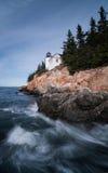 Il faro su una costa rocciosa con lo schianto ondeggia nella priorità alta Fotografie Stock