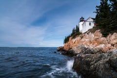 Il faro su una costa rocciosa con lo schianto ondeggia nella priorità alta Fotografia Stock