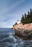 Il faro su una costa rocciosa con lo schianto ondeggia nella priorità alta Fotografie Stock Libere da Diritti