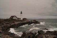 Il faro su una costa rocciosa con lo schianto ondeggia nella priorità alta Fotografia Stock Libera da Diritti