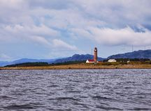 Il faro sulla riva in Norvegia con le montagne in backgrou immagine stock