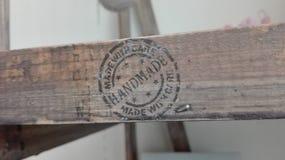 Il ` fatto a mano del ` dell'iscrizione con attenzione su un pezzo di mobilia di legno fotografia stock