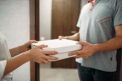 Il fattorino della pizza dà la scatola al cliente femminile immagini stock
