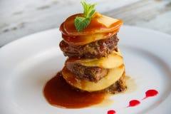 Il fegato del vitello con le mele ha posto gli strati con salsa su un piatto bianco Immagine Stock Libera da Diritti