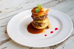 Il fegato del vitello con le mele ha posto gli strati con salsa su un piatto bianco Fotografia Stock Libera da Diritti