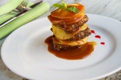 Il fegato del vitello con le mele ha posto gli strati con salsa su un piatto bianco Immagini Stock Libere da Diritti