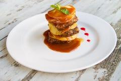Il fegato del vitello con le mele ha posto gli strati con salsa su un piatto bianco Fotografia Stock