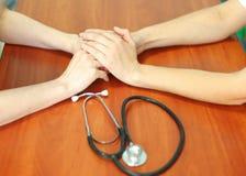 Il ` femminile s di medico passa a tenuta la mano paziente del ` s per incoraggiamento e l'empatia Associazione, fiducia e concet immagini stock