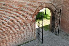 Il ferro aperto ha forgiato il cancello con il muro di mattoni Fotografia Stock