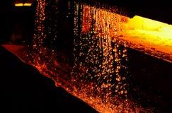 Il ferro caldo in smeltery ha tenuto da un lavoratore Fusione del metallo in un'acciaieria fotografia stock libera da diritti