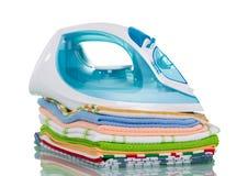 Il ferro da stiro sta sulla balla degli asciugamani di cucina rivestiti di ferro, isolata su bianco Fotografia Stock