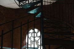 Il ferro forgiato ha torto le scale con la riflessione su un muro di mattoni rosso, i corrimani di vecchia costruzione d'annata,  Immagini Stock Libere da Diritti