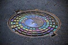 Il ferro ha fuso le botole in un asfalto che pavimenta con l'olio colorato immagini stock libere da diritti