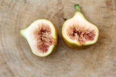 Il fico comune fruttifica aperto tagliando mostrando la carne su fondo di legno, vista superiore immagini stock libere da diritti