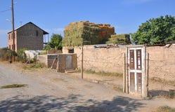 Il fieno sta asciugandosi nel cortile della costruzione di appartamento Lusarat, Armenia Fotografia Stock