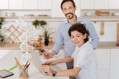 Il figlio affascinante e suo il padre che fanno una scuola proiettano insieme Fotografia Stock