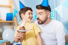 Il figlio allegro che guarda suo padre spegne la candela sul dolce fotografia stock