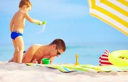 Il figlio allegro sparge la sabbia sul padre, spiaggia Fotografie Stock