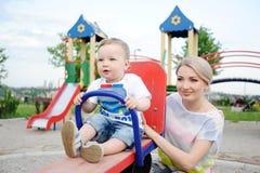 Il figlio del bambino e della mamma gioca nel campo da giuoco Fotografia Stock