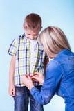 Il figlio del vestito da aiuto della madre fissa i bottoni Fotografie Stock Libere da Diritti