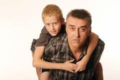 Il figlio di dieci anni allegramente ha abbracciato suo padre che si siede sul suo indietro Fotografia Stock