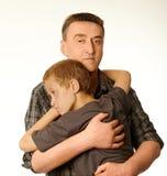 Il figlio ed il padre dei dieci anni si abbracciano Fotografie Stock Libere da Diritti