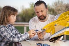 Il figlio ed il padre hanno fatto l'aeromodellino radio-controllato casalingo ai Immagine Stock Libera da Diritti