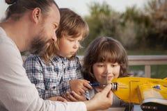 Il figlio ed il padre hanno fatto l'aeromodellino radio-controllato casalingo ai Fotografie Stock