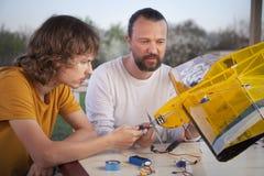 Il figlio ed il padre hanno fatto l'aeromodellino radio-controllato casalingo ai Immagini Stock Libere da Diritti