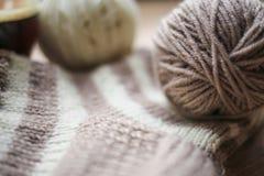 Il filato beige e bianco, Knitted ha barrato il calzino beige-beige è sulla tavola fotografie stock libere da diritti