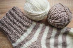 Il filato beige e bianco, Knitted ha barrato il calzino beige-beige è sulla tavola fotografia stock libera da diritti
